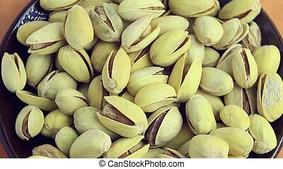 Salty roasted pistachios on a ceramic saucer - Salty roasted...