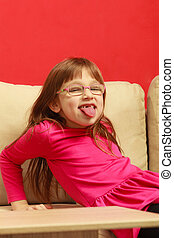 Toddler girl sitting on sofa sticking tongue out -...