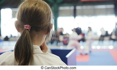 Teenager karate sports girl looking to fight on tatami - spectator - Karate competition