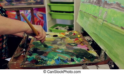 Woman artist mixes oil paints on a palette and draws a...