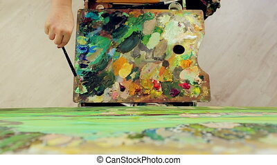 A woman paints a landscape with oil paints with a palette...