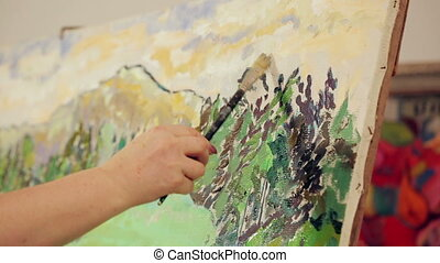 Artist paints a picture of oil paint brush in hand with palette