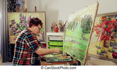 A woman paints a landscape with oil paints with a palette and brush.