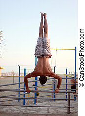 Man showing impressive strength, doing a handstand in beach