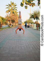 Man showing impressive strength, doing a handstand in street