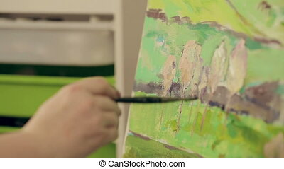 Artist paints a picture of oil paint brush in hand with...