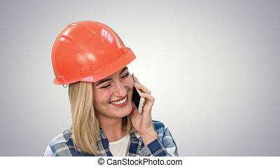 Beautiful female engineer in hardhat calling via cellphone...