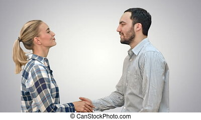 Teen people shaking hands and looking at camera on white...