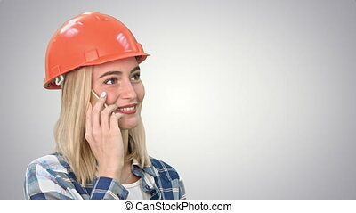 Beautiful happy woman in orange hardhat have a phone call via smartphone and smiling on white background.