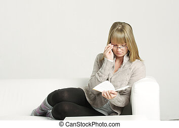 Woman in eyeglasses on sofa reading book