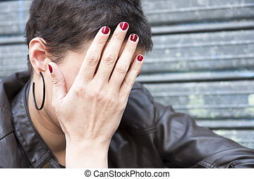 young woman hiding her face behind her right hand