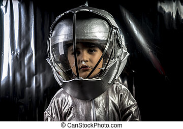 Science, Boy playing to be an astronaut with a space helmet and silver suit on metallic background