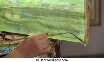 The artist writes a signature on the picture. Woman finished painting oil painting