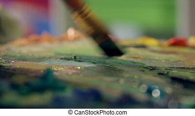 The artist mixes oil paints on a palette close up