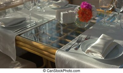Dining table, vase with flowers. Tableware and white napkin.