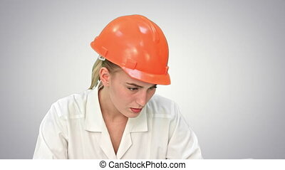 Stressed female engineer in helmet checking constraction plan on white background.