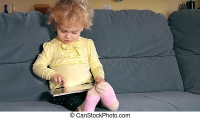 Cute little girl using tablet sitting on sofa and hand take...