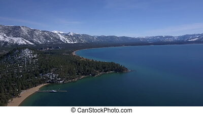 Lake Tahoe coastline and mountains covered by snow - Aerial...