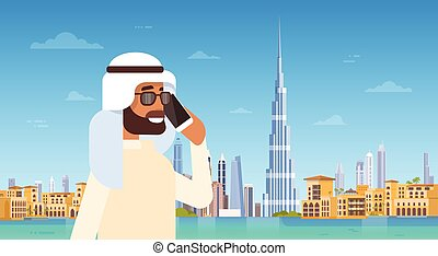 Arab Man Speaking On Cell Smart Phone Call Over Dubai Skyline Panorama, Modern Building Cityscape
