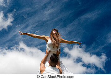 young couple dancing on sky background, freedom and relax...