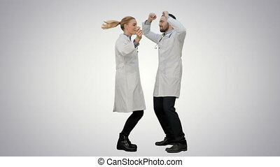 Two funny medical doctors with funny energy dance on white background.