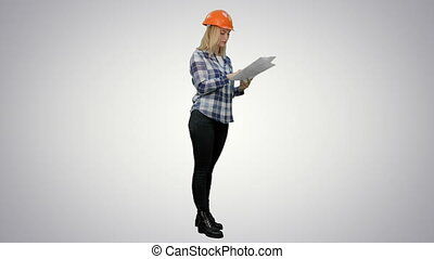 Young engineer woman reading technical drawings and analyze...