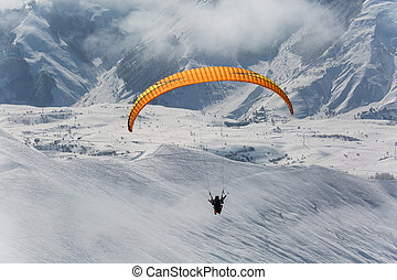 Parachute sky-diver flying in clouds above mountains with...