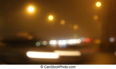 Blurred lights of city in fog and cars on road.