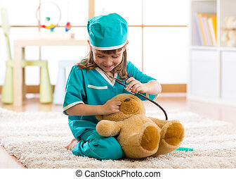 Cute kid girl playing doctor with plush toy at home - Cute...