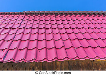 The roof of the country house is covered with metal roofing