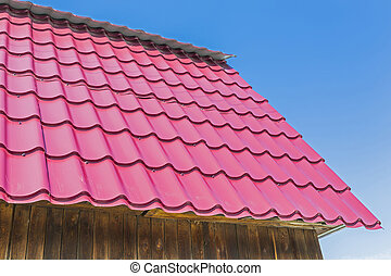 The roof of the country house is covered with metal roofing....