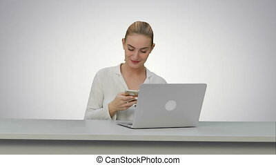 Happy woman is dancing on her own using smartphone at work place on white background.