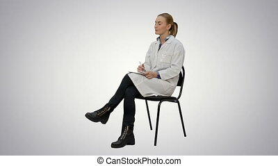 Female doctor talking to a patien and writes in a notebook on white background.