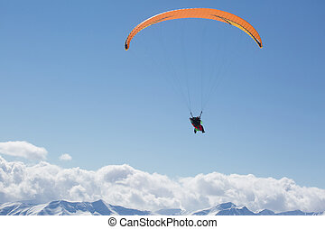 Parachute sky-diver flying in clouds above mountains. Travel...