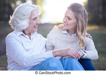 Loving woman enjoying conversation with elderly mother in...