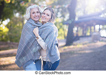 Charming woman hugging retired mother in the park - Like two...