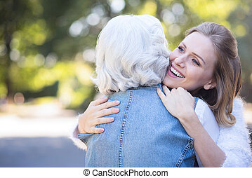 Happy young woman hugging retired mother in the park - Love...