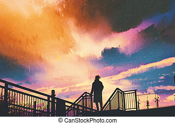 man standing on footbridge against colorful sky - silhouette...