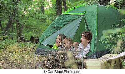 Girls and the little boy admire the nature lying in tent. -...