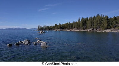 Flying over the surface of Lake Tahoe with boulders in water
