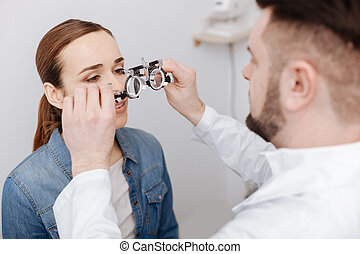 Professional male ophthalmologist preparing to do an eye test