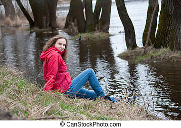 A walk by the river - Young girl sitting on the river bank