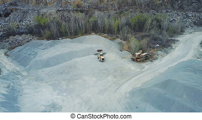 A bulldozer loads rubble in a stone quarry. Aero survey With...