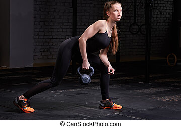 Sporty young woman with muscular body doing crossfit workout...