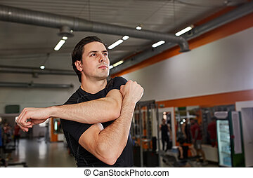 Full-length of young man in black sportswear stretching his...