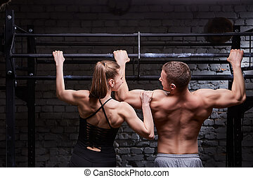 Rear photo of young attractive caucasian crossfit man and woman while working out in gym