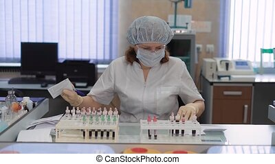 Blood test tubes being analyzed and interchanged by a laboratory worker. Work in the medical laboratory at the hospital. A woman in a protective mask and glasses sorts the patient's blood sample.
