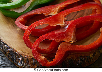 Green and red pepper slices on cutting board - Green and red...