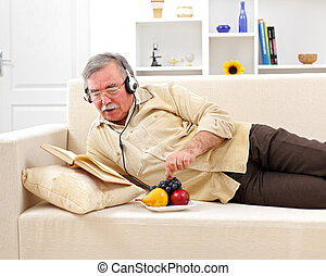 Senior man relaxing and reading - Senior man laying on sofa,...