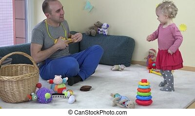 father play with toy guitar and cute baby daughter dancing. 4K